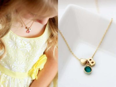 A Child Wearing Gold Initial Birthstone Necklace