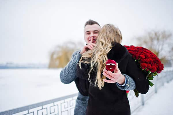 Man Making a Proposal With Diamond Engagement Ring and 101 Red Roses on Snowy Day