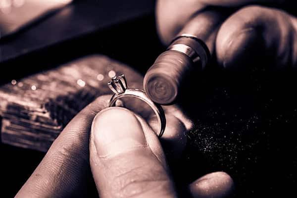Man Polishing a Diamond Platinum Wedding Ring - Jewelry Craft