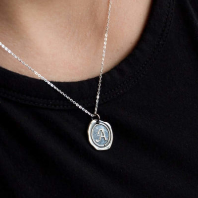 Antique-Looking Wax Seal Initial Pendant Necklace Paired With Black Collared Shirt