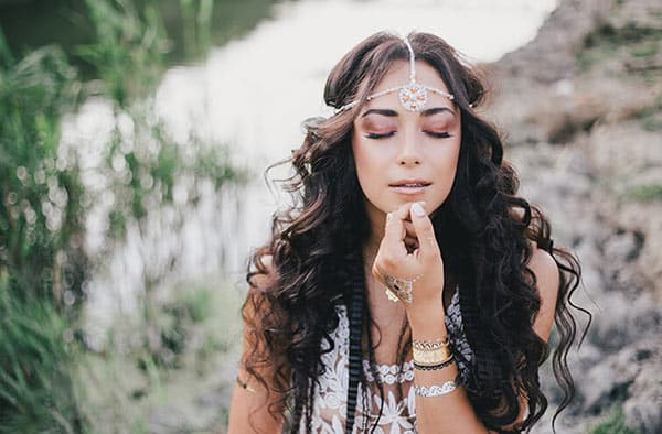 Beautiful Woman With Long Curly Hair Wearing Boho Jewelry and Dressed in Boho Style Dress