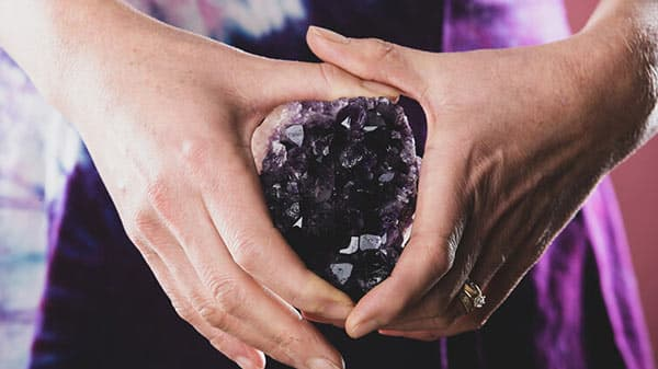 Holding Amethyst Purple Crystal in Hands