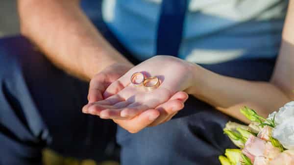 Groom and Bride Hold Their Rose Gold Wedding Bands