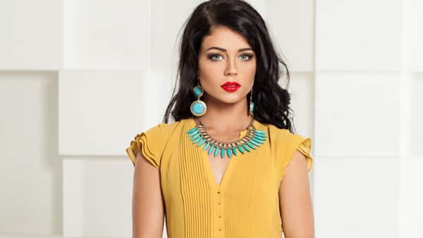 Woman Wearing Blue Turquoise Earrings and Necklace With Yellow Dress