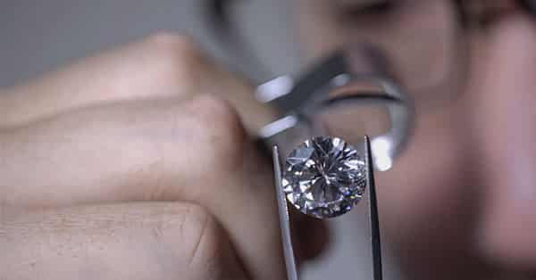 A Gemologist Inspecting the 4Cs of a Diamond With a Loupe