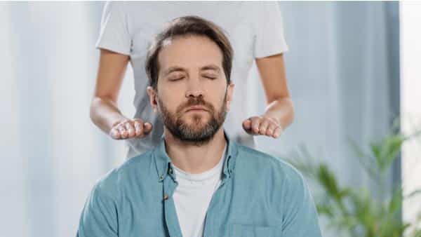 Man With Closed Eyes Sitting and Joining a Reiki Session