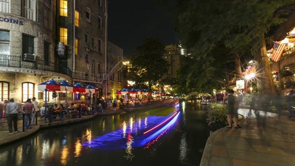 Boats Travelling on the San Antonio River Walk at Night