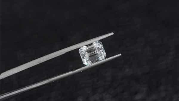 Inspecting an Emerald Cut Diamond With Tweezers